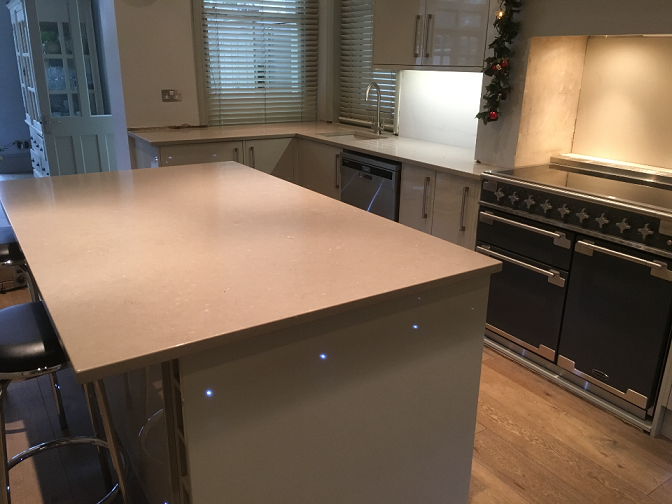 Large Island with overhang on stone counter top for seating. LED strip lighting under cupboards
